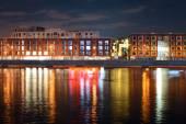 Fotografie Noční pohled z druhé strany řeky od provozních budov a reflexe na vodu z okna světlo