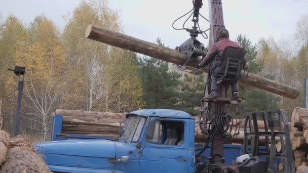 Vykládka dřeva s předním nakladačem. Stavební dřevo.