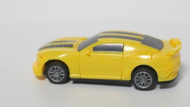 Natáčení auta s hračkami. Model žlutého sportovního auta je na točícím se stole.
