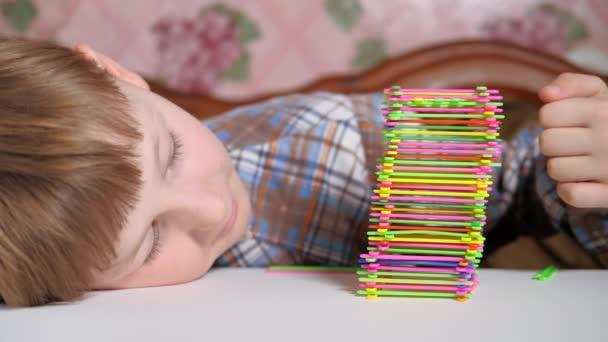 Junge baut eine Pyramide aus bunten Stöcken. Tischspiele.