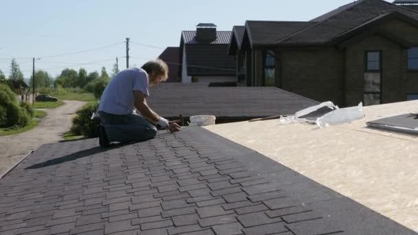 Dachdeckerarbeiten. Befestigung mit Nägeln und einem Hammer des Dachmaterials.