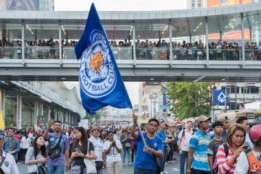 Supporter waves the Leicester City FC flag while waiting the parade