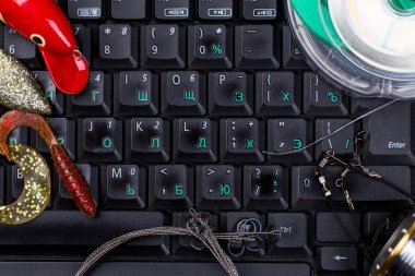 fishing tackles, line, lure, swimbait on keyboard