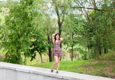 young beautiful smiling girl posing while standing in the park