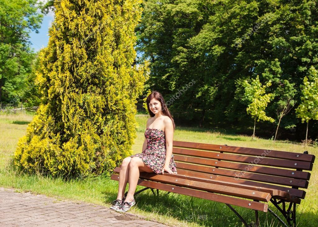 Jeune fille belle, assis sur un banc dans le parc de lété