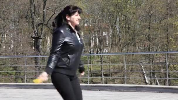 Mladá krásná žena, skákání přes švihadlo v city parku closeup