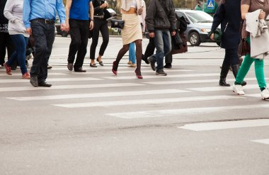 legs of pedestrians on a pedestrian crossing