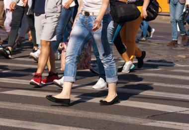 feet of pedestrians walking on the crosswalk