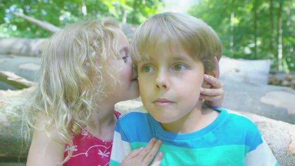 girl whispers a secret in boys ear