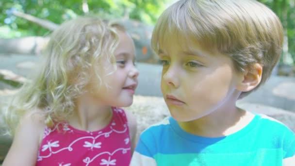 dívka šeptá tajemství chlapce do ucha