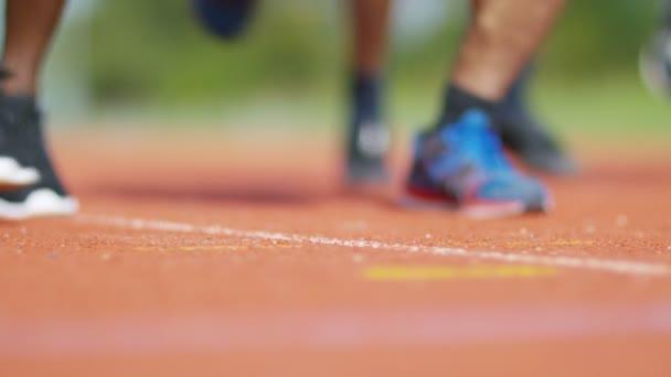 nohy běžců na běžecké dráze