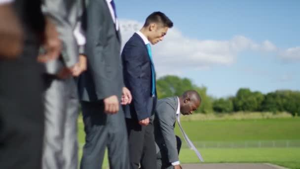 businessmen at running track line up at starting line