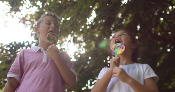 chlapec a dívka jíst lízátka