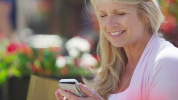 donna matura che esamina telefono mobile