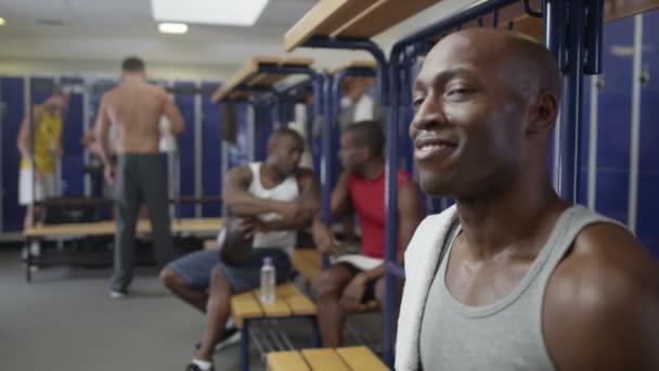 usmívající se muž sedící v šatně tělocvičny