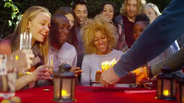 žena sfoukne svíčky na její narozeniny