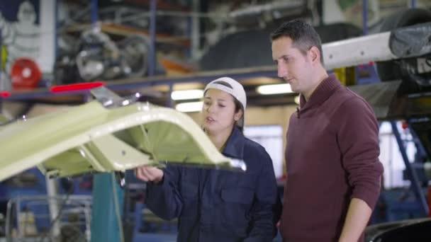Mechanik v garáži, mluví se zákazníkem