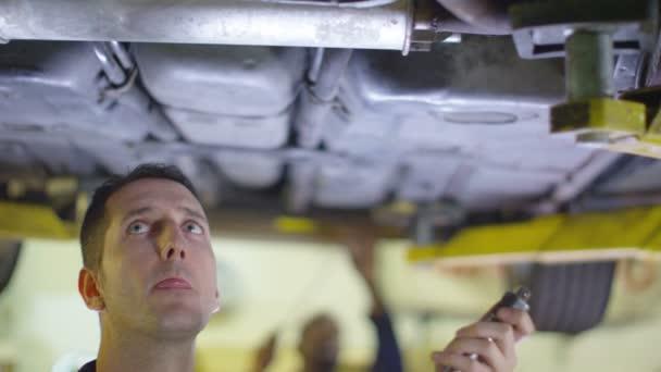 Mechanik, pracující pod auto