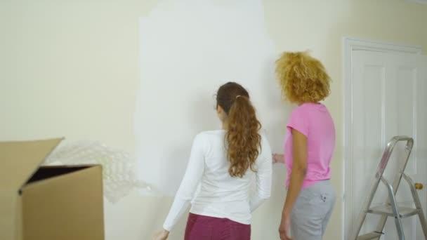 Vrouwen schilderij een muur in nieuwe woning u stockvideo
