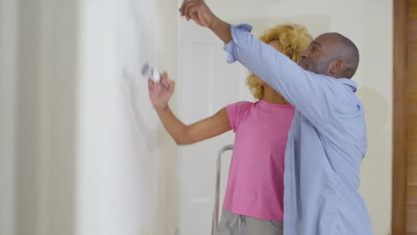 Paar schilderen een muur in nieuwe woning u stockvideo