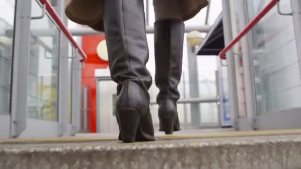woman walking up steps to a train