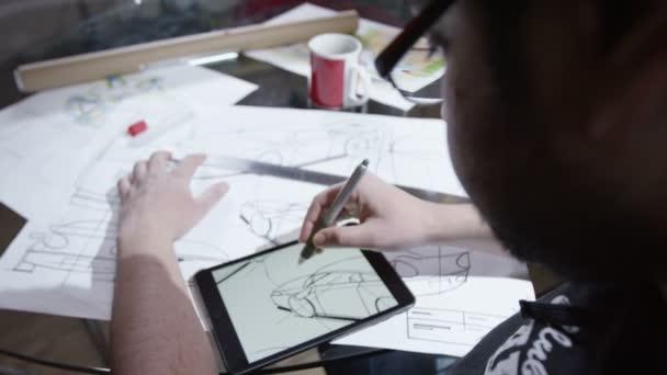 Člověk s použitím tabletu s výkresy automobilového designu