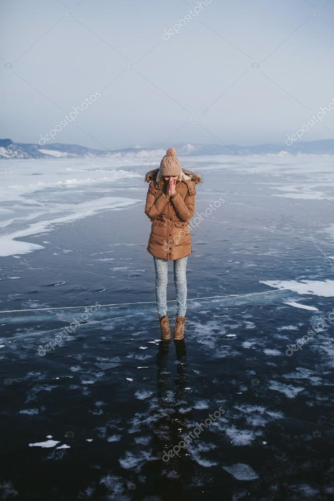 girl stands on pure ice of the frozen lake
