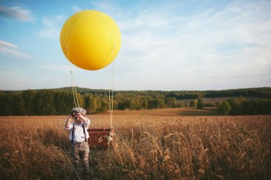 Little traveler boy looks through a telescope next to the balloon in a field
