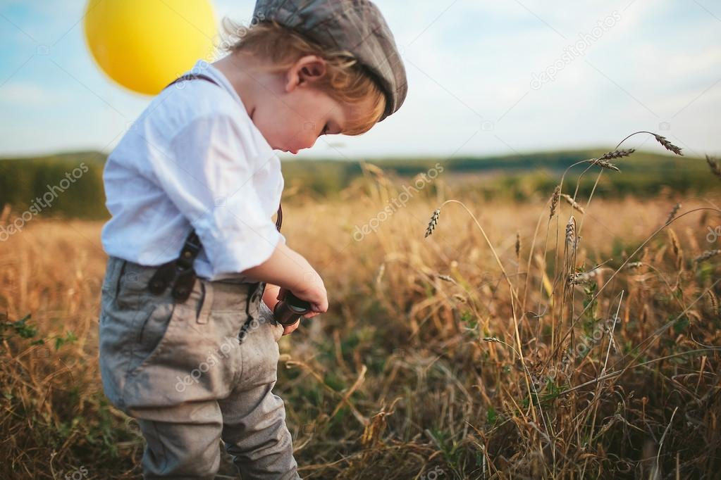 little boy traveler cleans spyglass in pocket, standing in a field