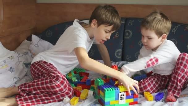 dva bratři v pyžamu hrající konstruktor na postel
