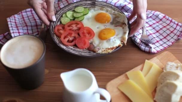 Ženské ruce, dát talíř na stůl se snídaní