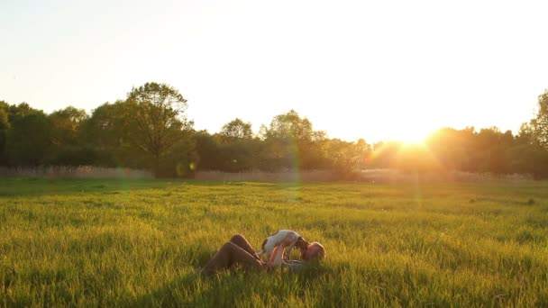 man lies with dog Jack Russell in the meadow at sunset