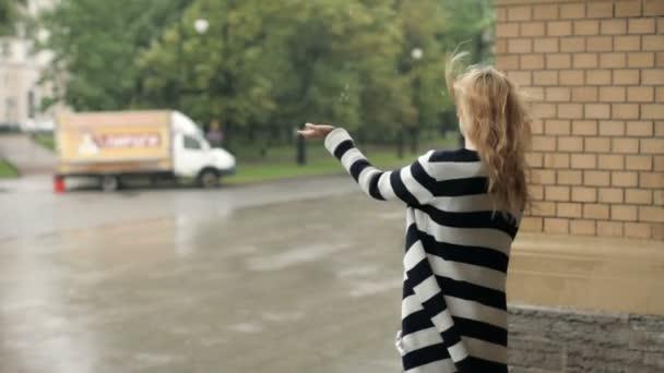 junges Mädchen mit Regenschirm läuft bei starkem Regen durch die Stadt