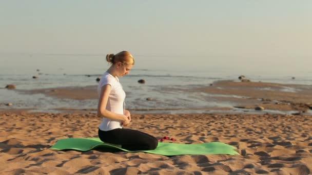 Žena praxe jógy na pláži
