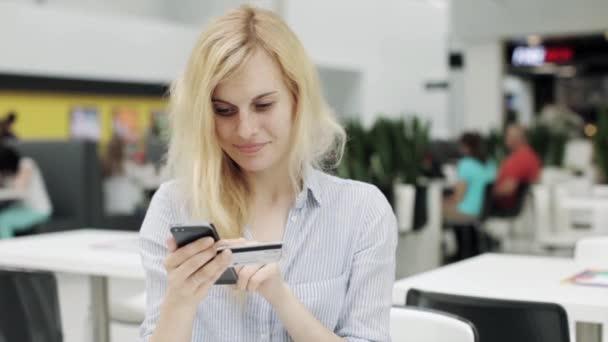 Žena pomocí Smartphone Online s kreditní kartou v nákupním centru