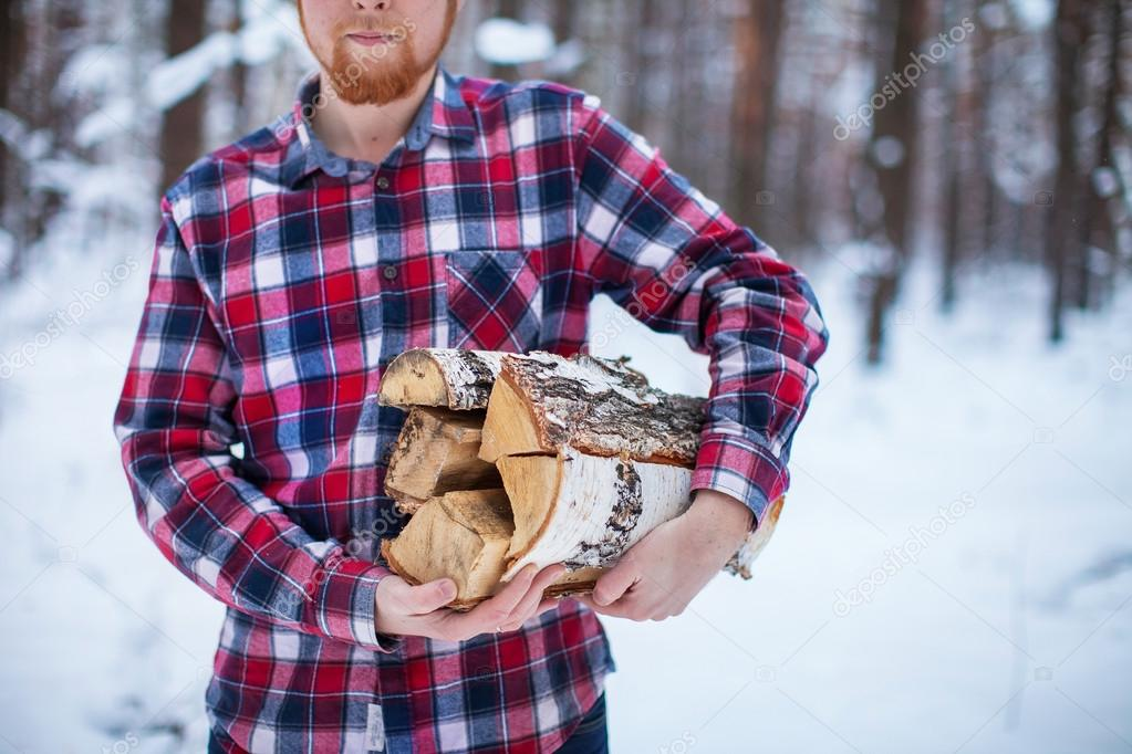 A man carries a pile of firewood in the winter forest