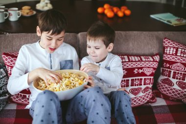 boys eating popcorn on a sofa in the dining room