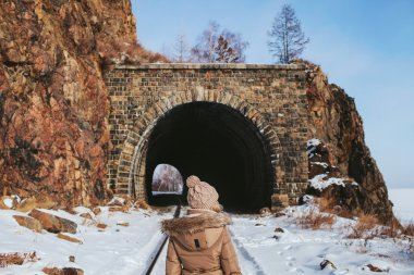girl is standing back on the rail in front of the tunnel in the rock