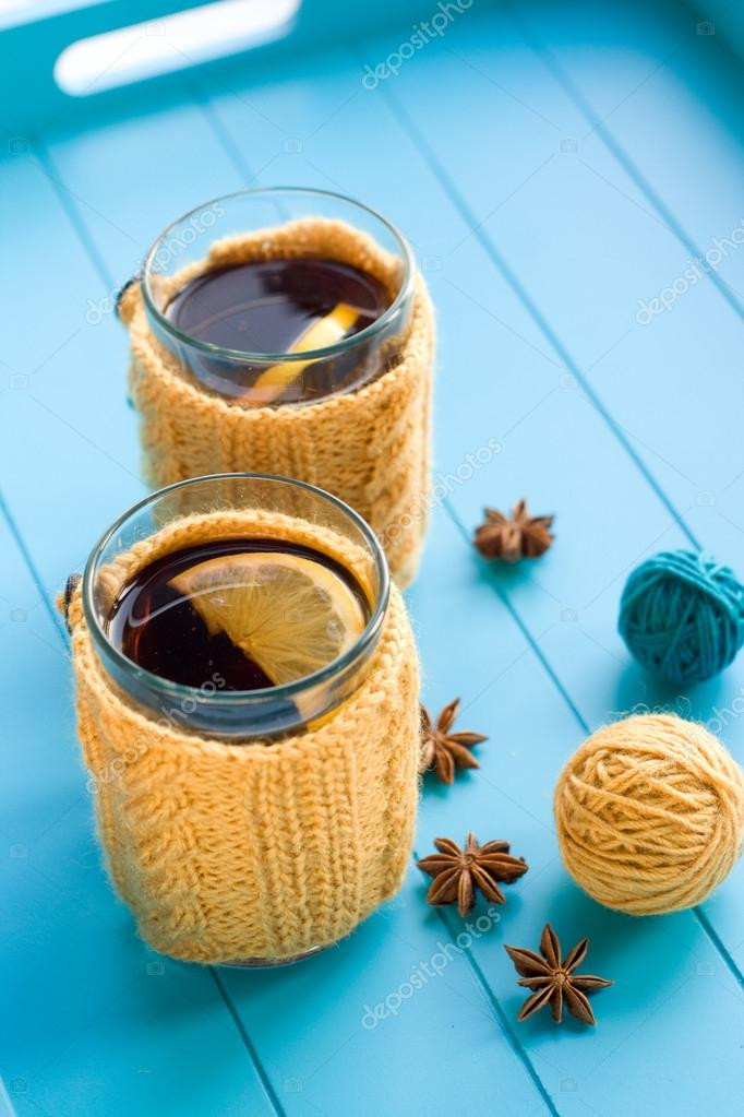 Two cups of tea in yellow Knitted sweaters on blue background