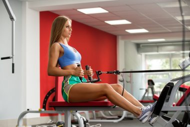 Workout in gym. Photo of girl looking like doll