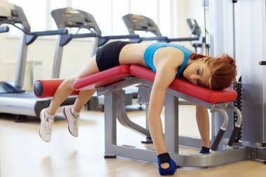 Tired sportswoman lying on sports bench