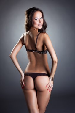Rear view of smiling model posing in bra and thong
