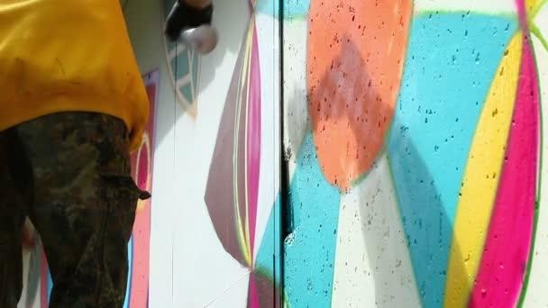 Mladý muž kreslení graffiti na zdi se sprejem