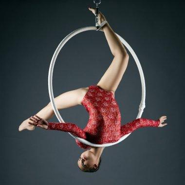 Lovely gymnast performs acrobatic stunt on hoop