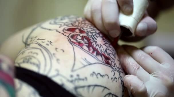 Tattooist nakreslí tetování červeným inkoustem, detail