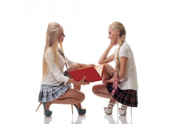 Two lovely blond schoolgirls posing in studio