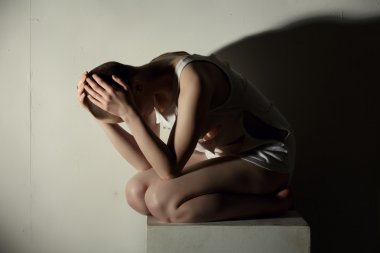 Mental illness. Shot of thin girl holding her head
