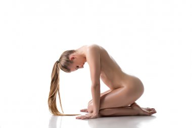 Nude pretty woman posing with her head bowed