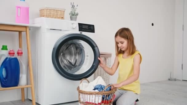 Kleines Mädchen lädt Kleidung in Waschmaschine