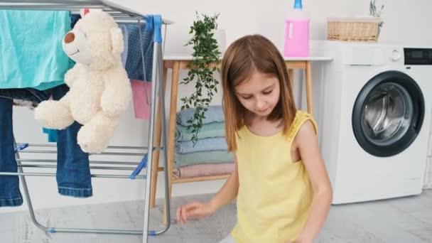 Kleines Mädchen hängt nassen Teddybär Spielzeug